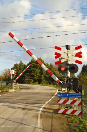 Railroad crossing on a winding road in the dutch countryside where the barriers are closing