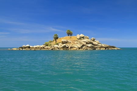 Dry uninhabited island off the coast of Thailand with a blue sky and turquoise sea