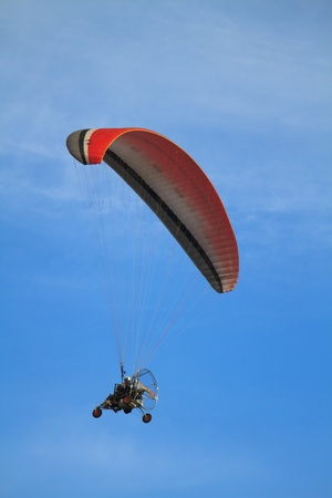 Couple power paragliding high above in the blue sky hanging under a red and blue parachute