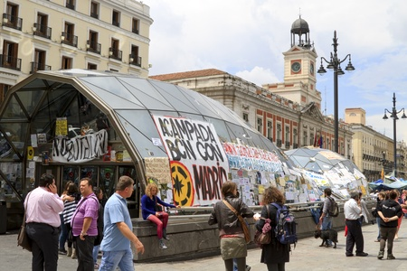 MADRID, SPAIN - JUNE 6: Protest posters pasted on the window of the metro station on Puerta del Sol Square June 6, 2011 in Madrid. These protests are known as the Spanish Revolution days in Madrid. Stock Photo - 9789638