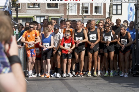 DORDRECHT, NETHERLANDS - SEPTEMBER 25 2011: Runners line up for the start of the 6th Drechtstedenloop in Dordrecht on September 25, 2011. The race is a 10km and 5km street circuit for all ages.