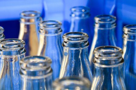 Empty bottles in a blue crate close up