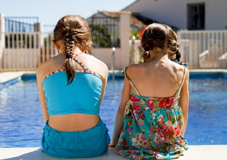 stitting: Two little sisters stitting side by side on the pool edge