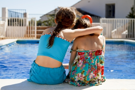 Two sisters ebracing each other by the pools edge Stock Photo