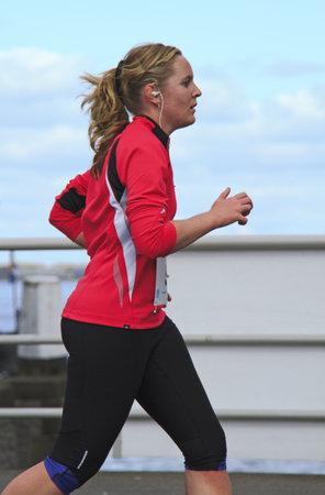 DORDRECHT, NETHERLANDS - APRIL 1 2012: The 65th edition ÔDwars door DortÕ on Sunday 1 April 2012. Female runner dressed in pink in the 10km race