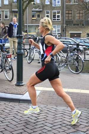 DORDRECHT, NETHERLANDS - APRIL 1 2012: The 65th edition �Dwars door Dort� on Sunday 1 April 2012. Female runner running through the centre of Dordrecht Stock Photo - 13096269