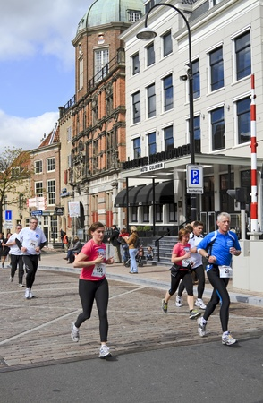 DORDRECHT, NETHERLANDS - APRIL 1 2012: The 65th edition �Dwars door Dort� on Sunday 1 April 2012. Runners passing Bellevue Groothoofd hotel in the 10km race in Dordrecht Stock Photo - 13096271