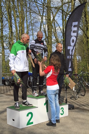 DORDRECHT, NETHERLANDS - APRIL 14 2012: Run Bike Run Bike Run duathlon event. John Aalbers, Armand van der Smissen and Remco Grasman receiving flowers on the winners podium on Saturday 14 April 2012. Stock Photo - 13257742