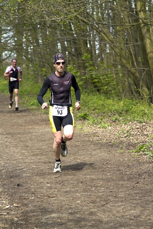 DORDRECHT, NETHERLANDS - APRIL 14 2012: Run Bike Run Bike Run duathlon event. Runners in the wooded part of the course of the dualthlon on Saturday 14 April 2012 in Dordrecht.
