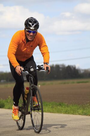 DORDRECHT, NETHERLANDS - APRIL 14 2012: Run Bike Run Bike Run duathlon event. A contender dressed in orange and black during the course of the dualthlon on Saturday 14 April 2012 in Dordrecht. Stock Photo - 13257708