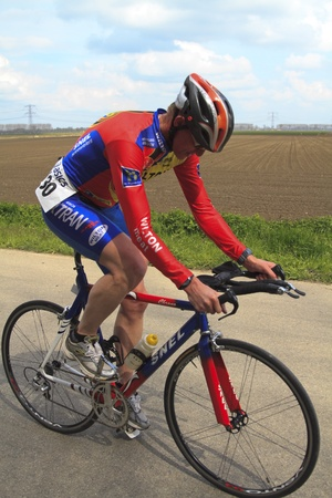 contender: DORDRECHT, NETHERLANDS - APRIL 14 2012: Run Bike Run Bike Run duathlon event. A contender dressed in red and blue cycling the course of the dualthlon on Saturday 14 April 2012 in Dordrecht.