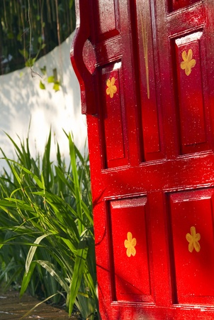 Bright red painted wooden gate leading to a lush tropical garden photo