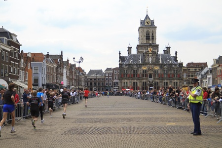DELFT, NETHERLANDS - MAY 17 2012: The 25th edition Trompper Optiek Golden Tenloop on Thursday 17 May 2012. Runners passing city hall in historic Delft Editorial