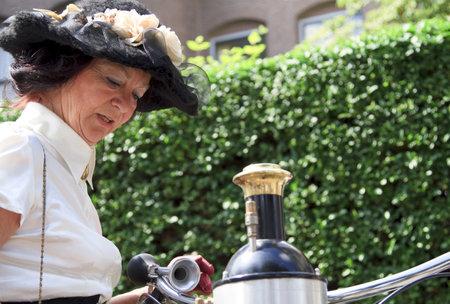 dordrecht: DORDRECHT, NETHERLANDS - JUNE 2 2012: Dordrecht in Steam, the largest steam power event in Europe. Women in period dress with a steam bicycle on Saturday 2 June 2012 in Dordrecht.