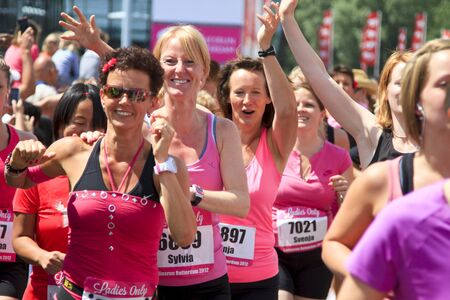 ROTTERDAM, THE NETHERLANDS - JUNE 10 2012: Runners cheer, smile and wave during the annual Ladiesrun 10 KM event held on Sunday June 10,  2012 in Rotterdam. Editorial