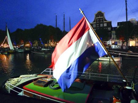 dordrecht: DORDRECHT, NETHERLANDS - JUNE 2 2012: Dordrecht in Steam, the largest steam power event in Europe. Dutch flag flying on a steamboat at night on Saturday  June 2 2012, in Dordrecht. Editorial