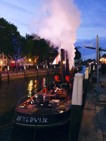 dordrecht: DORDRECHT, NETHERLANDS - JUNE 2 2012: Dordrecht in Steam, the largest steam power event in Europe. Steamboat Beverwijk moored at night on Saturday 2 June 2012 in Dordrecht.