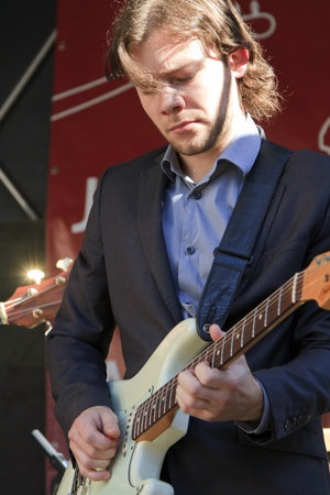 DORDRECHT, NETHERLANDS - JULY 15: Martijn Smit dressed in a suit plays guitar live on stage for The Jig at the Big Rivers Festival on Sunday 15 July 2012 in Dordrecht.