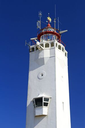White and red lighthouse on the dutch coast in Noordwijk photo