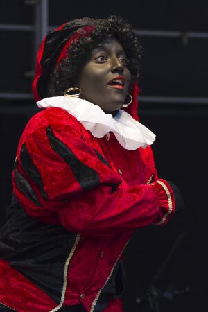 DORDRECHT, NETHERLANDS - NOVEMBER 12: Woman dressed as Zwarte Piet entertaining children on Saint Nicolas parade on November 12, 2011 in Dordrecht, Netherlands. Stock Photo - 16232602