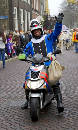 DORDRECHT, THE NETHERLANDS - NOVEMBER 18: Motorcycle policeman dressed in costume waving to the children on November 18, 2012 in Dordrecht, Netherlands. He is escort to Santa Claus in a parade.