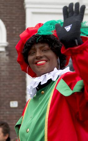 DORDRECHT, NEDERLAND - NOVEMBER 18: Vrouw gekleed als Zwarte Piet zwaaien naar de kinderen in een optocht in de straten van Dordrecht op 18 november 2012 in Dordrecht, Nederland. Redactioneel