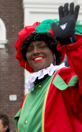 DORDRECHT, THE NETHERLANDS - NOVEMBER 18: Woman dressed as Black Piet waving to the children in a parade on the streets of Dordrecht on November 18, 2012 in Dordrecht, Netherlands.