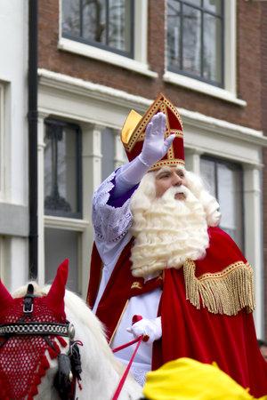 DORDRECHT, NEDERLAND - NOVEMBER 18: Saint Nicolaas op zijn witte paard te rijden door de straten van Dordrecht zwaaien naar de kinderen op 18 november 2012 in Dordrecht, Nederland.
