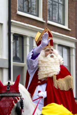 DORDRECHT, NETHERLANDS - NOVEMBER 18: Saint Nicolaas on his white horse riding through the streets of Dordrecht waving to the children on November 18, 2012 in Dordrecht, Netherlands. Redactioneel
