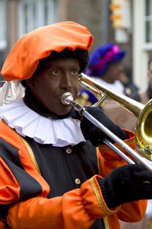 DORDRECHT, NEDERLAND - NOVEMBER 18: man verkleed als Zwarte Piet met trombone spelen in een parade vieren van de komst van de kerstman in Nederland op 18 november 2012 in Dordrecht, Nederland.