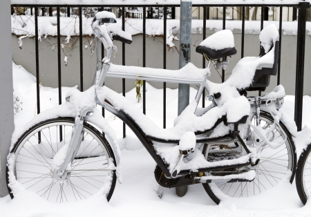 Bicycle with infant seat covered in snow leaning against a fence photo