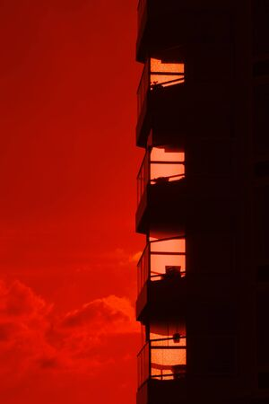 Building silhouette of a high rise flat against a burning red sunset