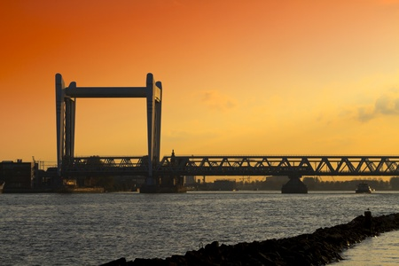 Railway bridge crossing the river the old maas in Dordrecht at sunset with a dramatic sky photo