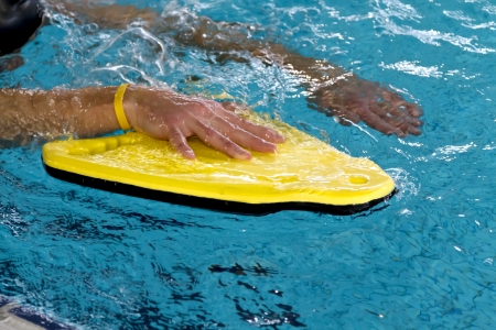 Man in swimming pool using a yellow buoy to train in swimming techniek Editorial
