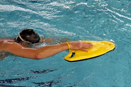 Man practicing swim techniek using a yellow float in swimming pool