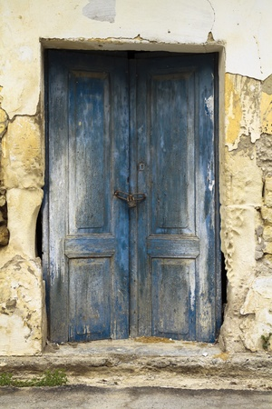 Old ruin with blue double wooden locked doors as building entrance photo