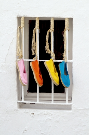 Four brightly colored shoes hanging outside a window Stock Photo