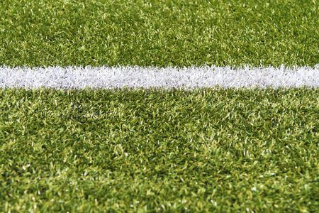 White stripe on a bright green artificial grass soccer field photo