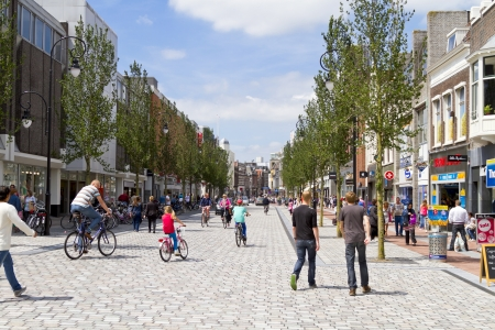 DORDRECHT, NETHERLANDS - JUNE 30, 2013: Busy shopping street with people walking and cycling in the sunny historic center of Dordrecht. The new shopping street was finished and opened in July 2013. Editorial