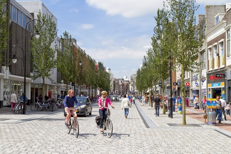 DORDRECHT, NETHERLANDS - JUNE 30: Busy shopping street with people walking and cycling in the sunny historic center on June 30, 2013 in Dordrecht. The new shopping street was opened in June 2013. Editorial