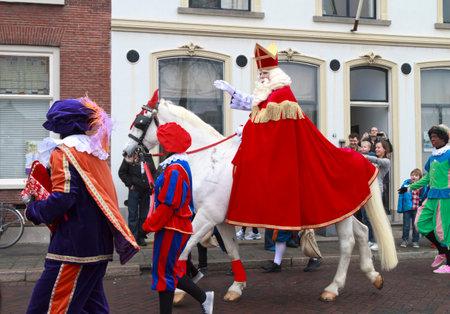 DORDRECHT, NEDERLAND - 17 november Sinterklaas op zijn witte paard rijden door de straten van Dordrecht met Zwarte Piet als escort zwaaien naar de kinderen op 17 november 2012 in Dordrecht, Nederland