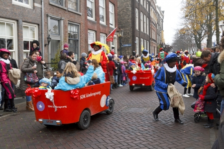 escorted: DORDRECHT, THE NETHERLANDS - NOVEMBER 17  Children being driven in carts escorted by Zwarte Piet dressed in costume giving presents to the children on November 17, 2012 in Dordrecht, Netherlands