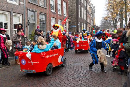 DORDRECHT, THE NETHERLANDS - NOVEMBER 17  Children being driven in carts escorted by Zwarte Piet dressed in costume giving presents to the children on November 17, 2012 in Dordrecht, Netherlands
