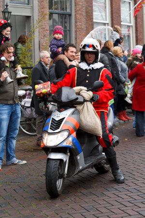 DORDRECHT, NEDERLAND - 17 november Motorcycle politieagent gekleed in kostuum het geven van cadeautjes aan de kinderen op 17 november 2012 in Dordrecht, Nederland Hij is een escorte naar Sinterklaas in de optocht