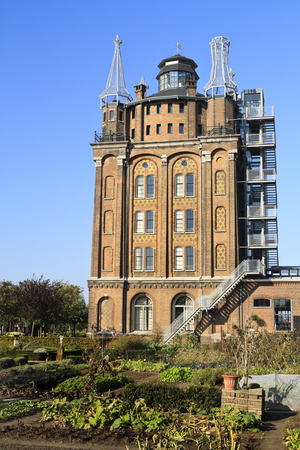 DORDRECHT, THE NETHERLANDS - OCTOBER 23, 2011  Old water tower, Villa Ausustus Hotel with vegetable garden in the foreground  It was rebuilt and converted into hotel and restaurant in 2007