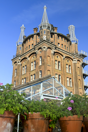 DORDRECHT, THE NETHERLANDS - OCTOBER 23, 2011  Old water tower, Villa Ausustus Hotel under a blue sky with gardens in the foreground  It was rebuilt and converted into hotel and restaurant in 2007