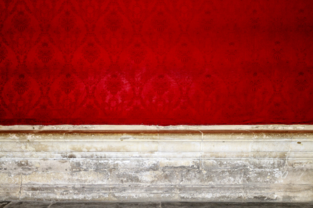 Empty room interior with red paterned wallpaper and carved stone edges and floor  photo