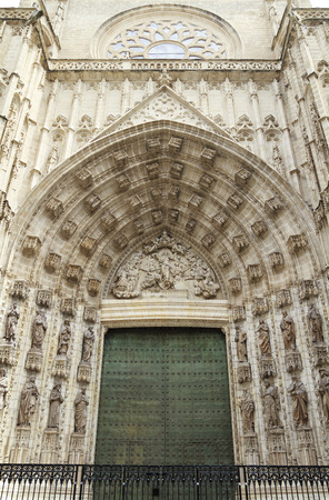 main gate: Beautiful carved bas-relief and green door of Assumption, Sevilla Cathedral