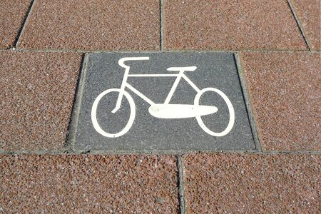 A pink colored tiled bicycle lane with a retro bike symbol imprint