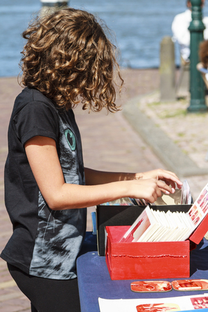 Dordrecht, The Netherlands - August 11, 2013  Young visitor to the art fair sorting through hand painted postcards on a stall  Place DAry is an annual art event held on the riverside in Dordercht